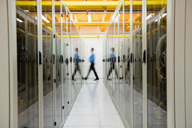 Technician walking in hallway of server room-1