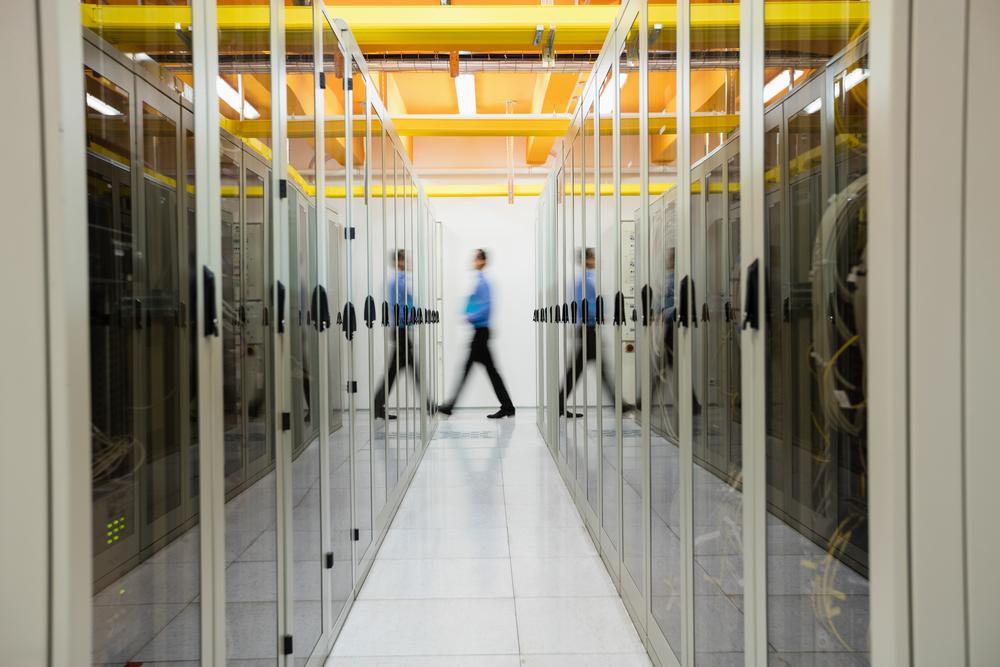 Data Center Systems Data Center Design Technician Walking Through Hallway of Servers